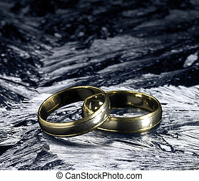 two golden wedding rings on ice surface - studio photography...