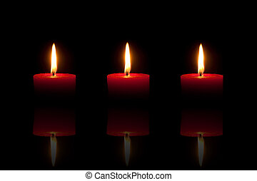 Three burning red candles in front of black background
