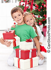 Siblings with lots of presents at christmas time