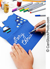 Child writing christmas greeting card - Child writing on...