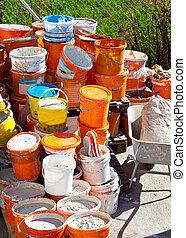 paint bucket after renovation - many buckets of paint by a...