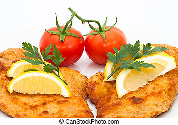 Schnitzel - Detail of schnitzel with lemons and tomatoes,...