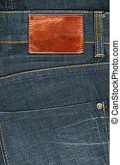 Highly detailed closeup of blank brown natural leather label on dark denim, good for background