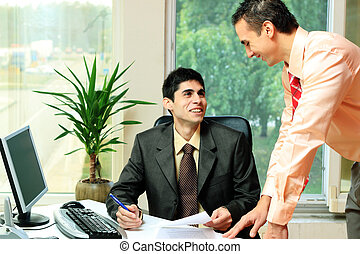 Two businessmen discussing tasks at office desk