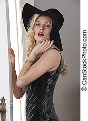 portrait of beautiful blond girl with curly hair and hat with black dress posing towards the camera near a white old fashion door