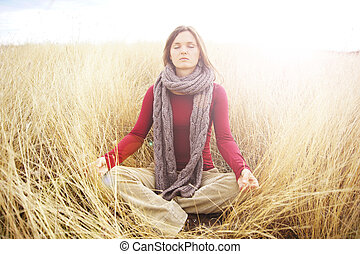 Within - Beautiful young woman meditating in a open field in...