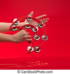 hands holding tambourine on red background - woman's hands...