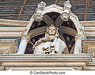 Statue of Virgin Mary on the façade of a church