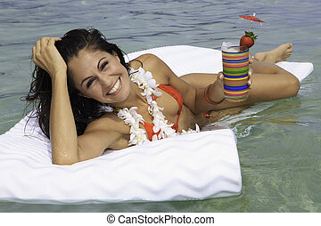 beautiful woman in bikini floating on a raft with a drink at...