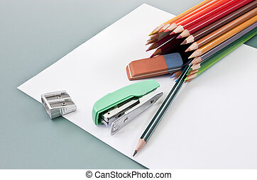 School supplies on a white paper outgoing of colored pencils tube
