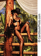 Young and sexy bikini model with hat in tropical...