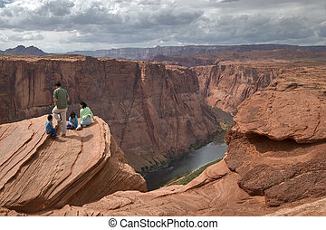 Above a chasm. - Group of tourists on edge of a deep canyon...