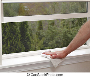 Reducing Allergies - Hand dusting a window sill to reduce...