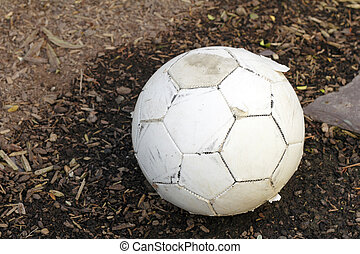 Worn Soccer Ball - A beat up sports toy outside on wood chip...