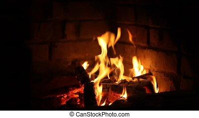 Fire in the dark - Firewood burning in the fireplace