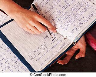 Student hands and notebook with pen at the desk