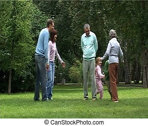 Playing outdoors - Children running near their parents and...