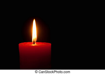 Burning red candle in front of black background