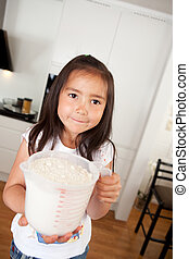 Young Girl Baking Measuring Cup of Flour - Child looking at...