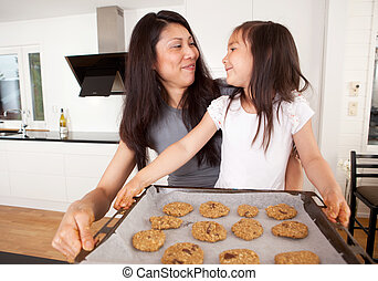 Mother and Daughter Baking Cookies - Mother and daughter...