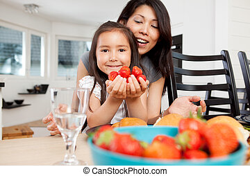 Mother and Daughter in Kitchen with Strawberries - Mother...