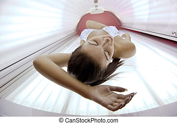 Beautiful young woman tanning in solarium - Beautiful young...