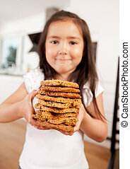 Young Girl Holding Stack of Cookies