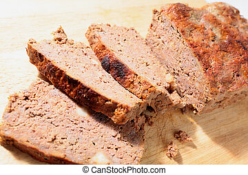 Meatloaf slices - A homemade meatloaf, sliced, on a chopping...