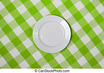 white round plate on green checked tablecloth