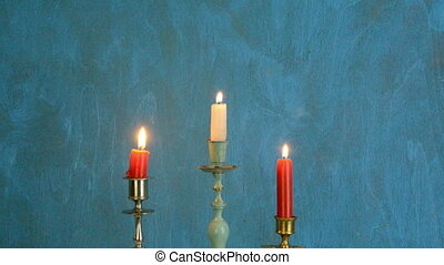 candles on blue background - three candlesticks with candles...