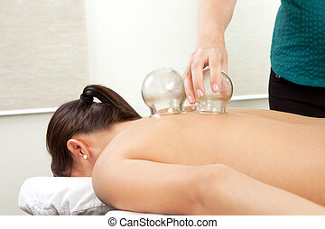 Fire Cupping - Woman receiving a cupping treatment at an...