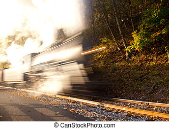 Steam train powers along railway - Abstract blur view of a...
