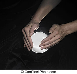 crystal ball and hands around - high angle shot of a glowing...