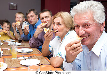 big family at table - portrait of a cute people eating pizza