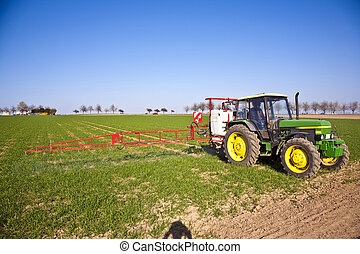 tractor on field sputtering pest protection on plants