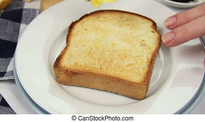 Buttering Toast - Butter being spread on a hot toast slice....