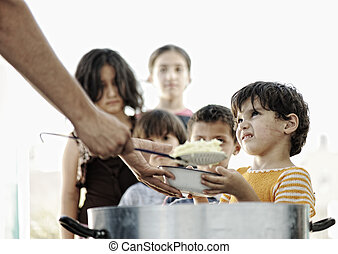 Hungry children in refugee camp, distribution of...