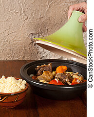 Tajine moroccan dish - Hand taking of the lid of a steaming...