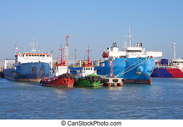 Cargo ships and guard boats docked in port - Front view of...
