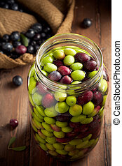 Olives in Brine (with Water and Salt in Glass Jar) on Wood