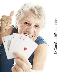 senior woman playing poker - portrait of senior woman...