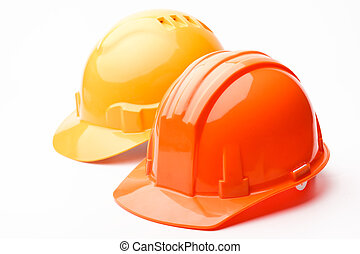 Hard hats - A pair of hard hats, yellow and orange, isolated...