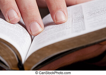 Reading Through the Bible - Close photo of man thumbing...