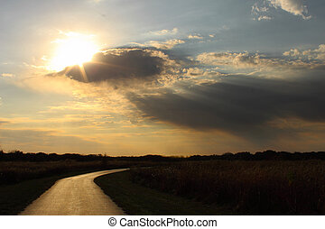 Sun through clouds on a lonely road - Scenic sunset breaking...