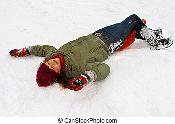girl lying in the snow from sledging down the hill in winter