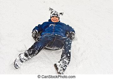 Boy lying in snow having fun