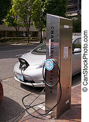 Electric car plugged into an public charging station in...