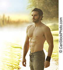 Man against light - Portrait of a beautiful shirtless man in...