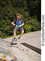boy has fun scooting in the scating at the skatepark