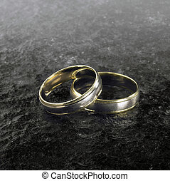 two golden wedding rings on stone surface - studio...